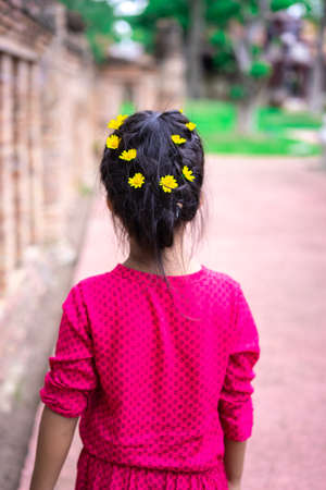 Back view of little asian girl in red dress with beautiful hair and yellow flower walking in the park 版權商用圖片