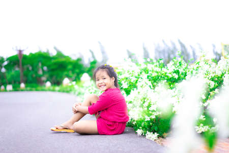 Portrait of happy asian little girl in red dress sitting on the street with beautiful flower on side road