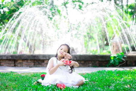 cute little asian girl in white dress holding a bear doll in the park 版權商用圖片