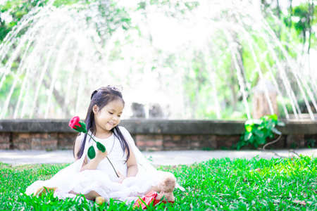 cute little asian girl in white dress with red rose and gift in the park