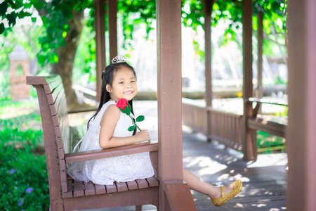 cute little asian girl in white dress holding a red rose sitting on a bench in the park