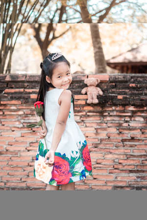 cute little asian girl in dress stand back and holding a red rose give to a bear in the park