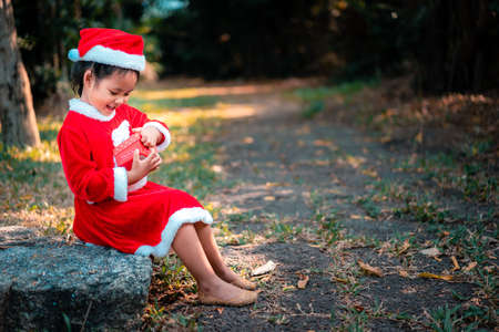 little asian girl in red Santa Claus costume feel surprise with present box in the park