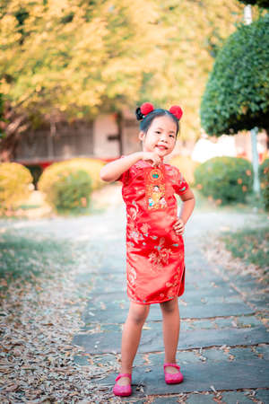 cute little asian girl in chinese traditional dress smiling and holding red envelope.Happy chinese new year concept. 版權商用圖片