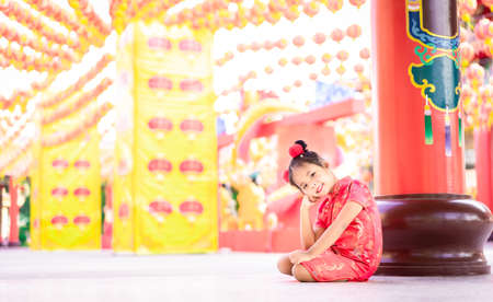 cute little asian girl in chinese traditional dress smiling and sitting in the temple.Happy chinese new year concept.