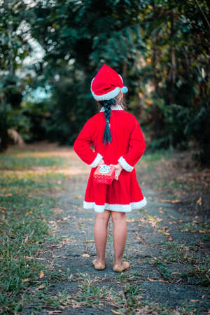 little asian girl in red Santa Claus costume stand back with present box in the park 版權商用圖片