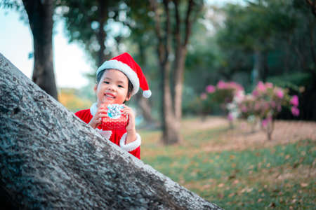 little asian girl in red Santa Claus costume with present box in the park