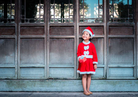 little asian girl in red Santa Claus costume with present box standing on wooden door  background