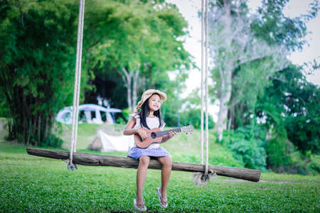little asian girl sitting on wooden swing playing ukulele while camping in nature park