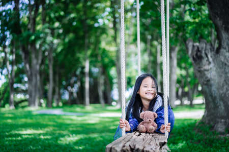 little asian girl in princess costume playing bear on wooden swing in the park