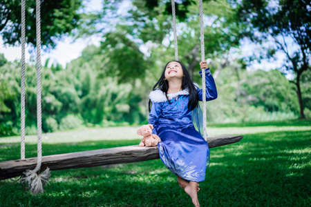 little asian girl in princess costume playing wooden swing in the park