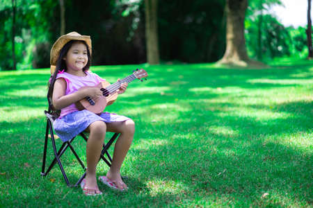 little asian girl sitting on chair and playing ukulele in the park 版權商用圖片