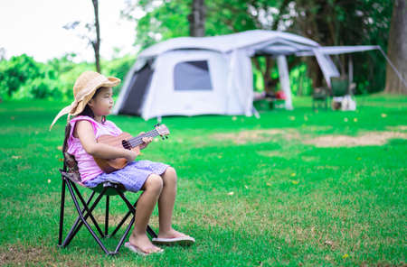 little asian girl playing ukulele or hawaiian guitar in the park while camping in summertime 版權商用圖片