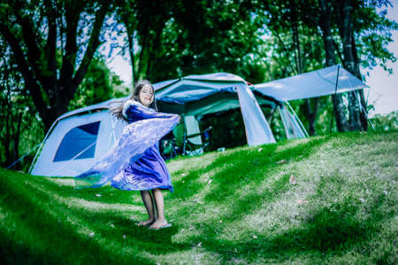 little asian girl in princess costume standing in front of tent while camping 版權商用圖片