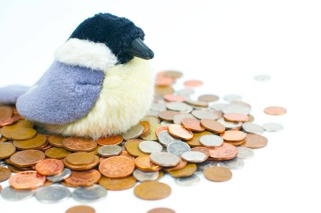 coppers: Toy bird sitting on a nest of British coins Stock Photo