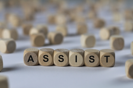 assist - cube with letters, sign with wooden cubes Stock Photo