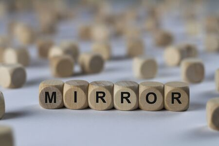 reproduce: mirror - cube with letters, sign with wooden cubes Stock Photo
