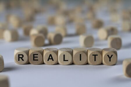 actuality: reality - cube with letters, sign with wooden cubes Stock Photo