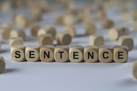 adjudicate: sentence - cube with letters, sign with wooden cubes