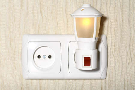 Small night lamp inserted into the socket
