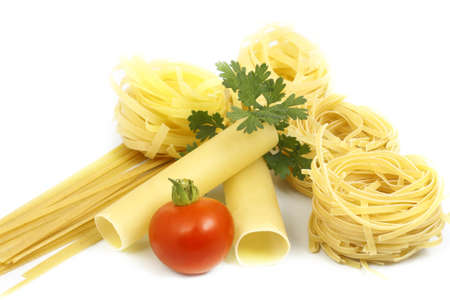 a variety of pasta with greens and tomato on white background