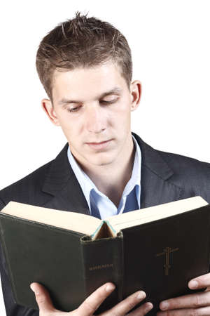 young guy in a suit holding a bible, isolated on a white background photo