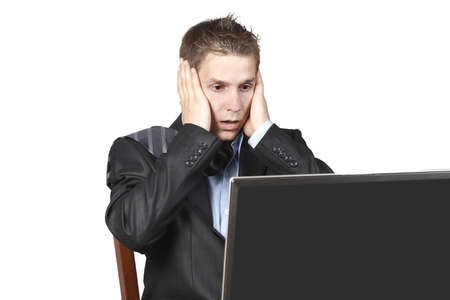 businessman sitting next to a laptop and was horrified to look at the screen, his head in his hands, isolated on a white background photo