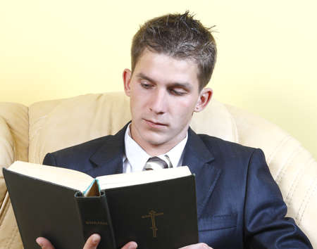 young guy in a suit, sitting on a leather couch and reads the Bible