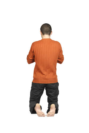 man praying: a man kneeling with his back, isolated on a white background