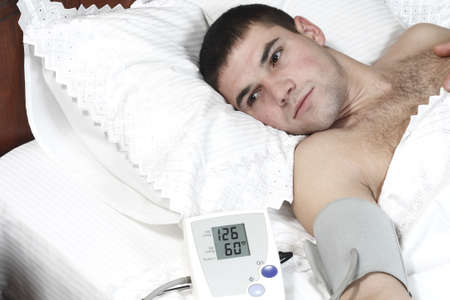 young guy lying on the bed measures the pressure