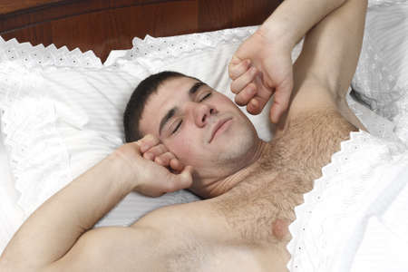 a young man stretching in bed  photo