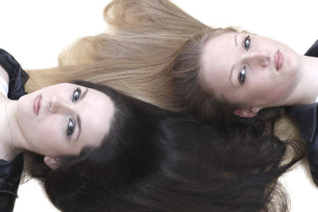 Two girls lie with her hair isolated on white background