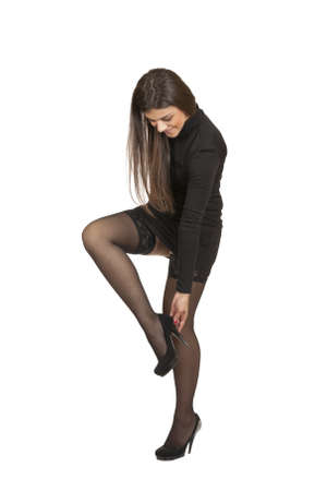 black stockings: young girl raised her leg to straighten shoes isolated on white background  Stock Photo