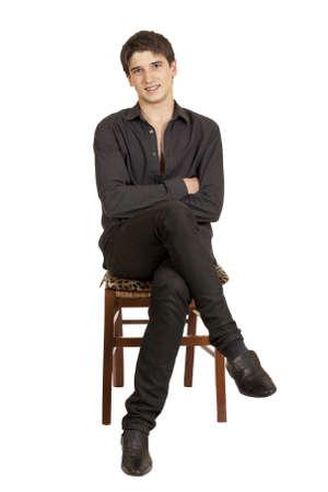 coupe de cheveux homme: un jeune homme assis sur une chaise isol�e sur fond blanc