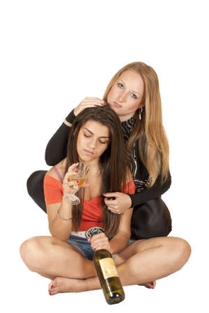 two beautiful girls with a bottle of wine isolated on white background photo
