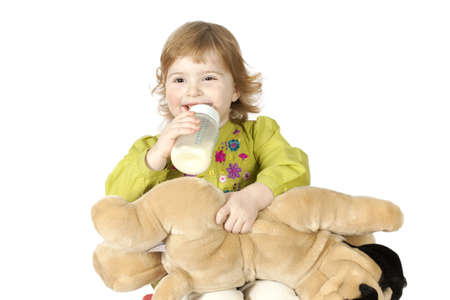 little girl drinking milk from a bottle isolated on white background photo