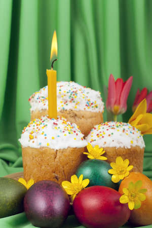 Colored eggs and Easter cakes with a lighted candle on a background of green tissue photo
