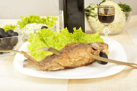 Fried fish carp salads wine and olives displayed on the table photo