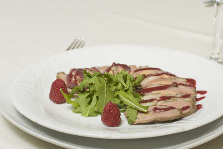 cutting of pork with raspberry sauce on a plate closeup