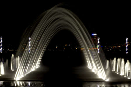 arched fountain in the background of  city at night, backlit closeup photo