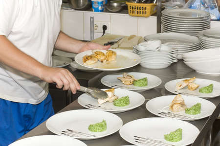 chef at the restaurant arranges food on a plate Stock Photo