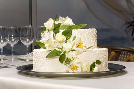 white wedding cake with fresh flowers on a metal tray