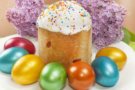 Easter cake and painted eggs with a sprig of lilac closeup Stock Photo