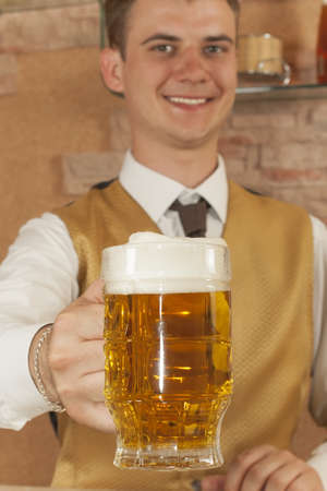 The waiter holds out hand forward with glass of of beer Stock Photo