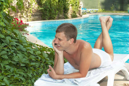 sunbed: young man talking on the phone on a sunbed beside the pool