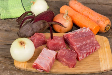 semifinished: fillet of carp with vegetables on the table with old rotten boards Stock Photo