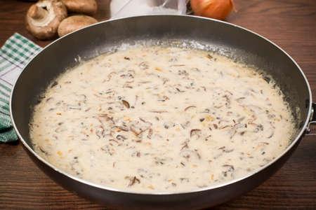 teflon: mushrooms in sour cream in a Teflon pan on the table Stock Photo