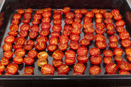 spread sheet: sun-dried tomato halves spread out on the baking sheet Stock Photo