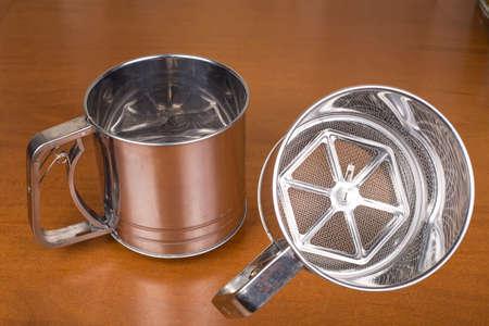 Mug - metal sieve for sifting flour closeup Stock Photo