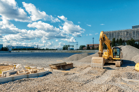 the image Tracked excavator on a construction site among piles of crushed stone